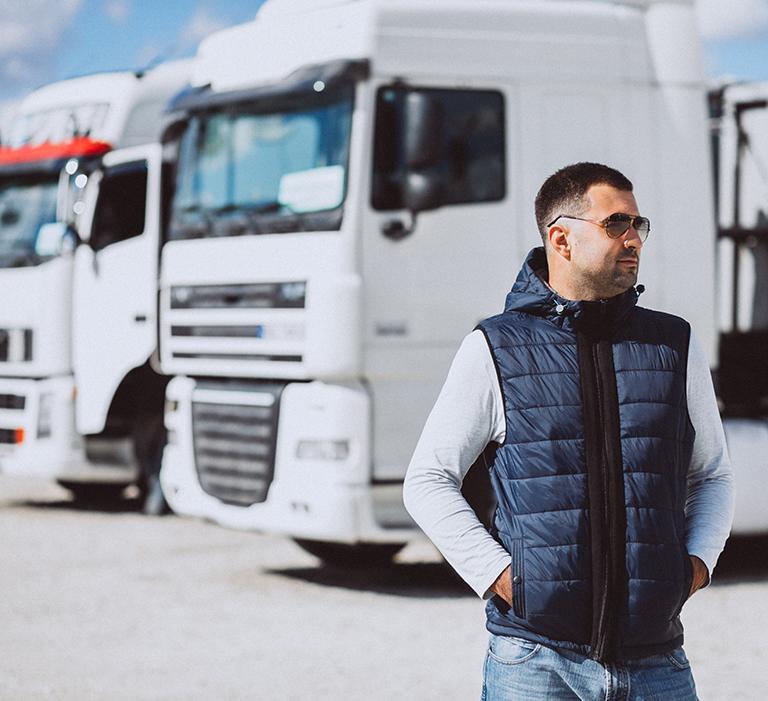 Muž napozadí nákladných automobilov
